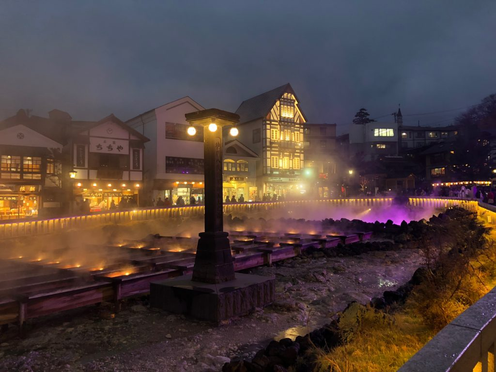 The yubatake at night. All the buildings are lit up, and the yubatake itself is lit with purple and yellow lights that rise up through the fog.