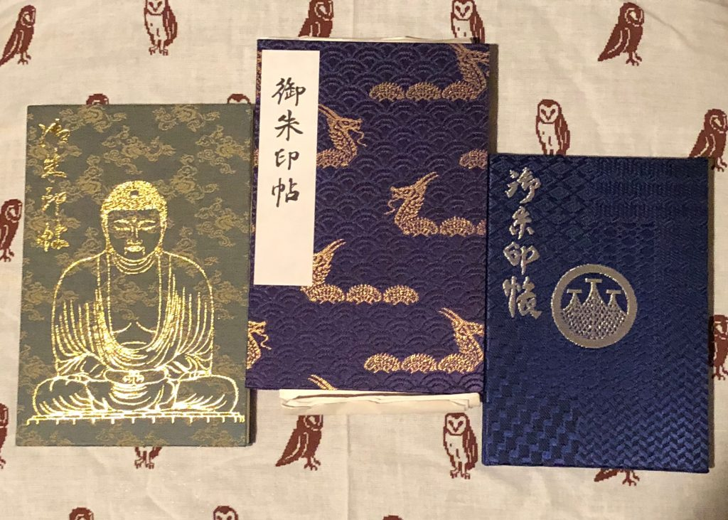 Three different goshuin books. The one on the far left is green with a golden Buddha statue stamped on it -- it's clearly from Kamakura. The one in the center is blue with golden dragons. The one on the right is the simplest design, blue with three towers in silver foil.