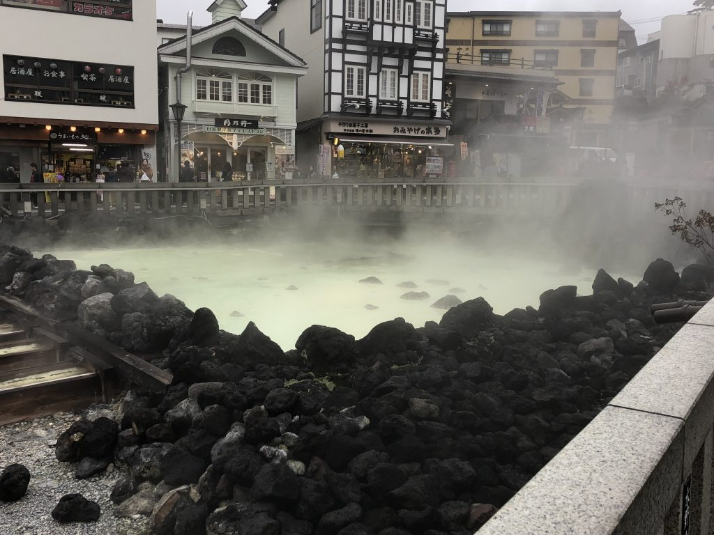 A hot spring shrouded in immense amounts of steam. Through the steam, you can see a pool of water that is a milky green. The pool is surrounded with black rocks. The town shops can be seen in the background.