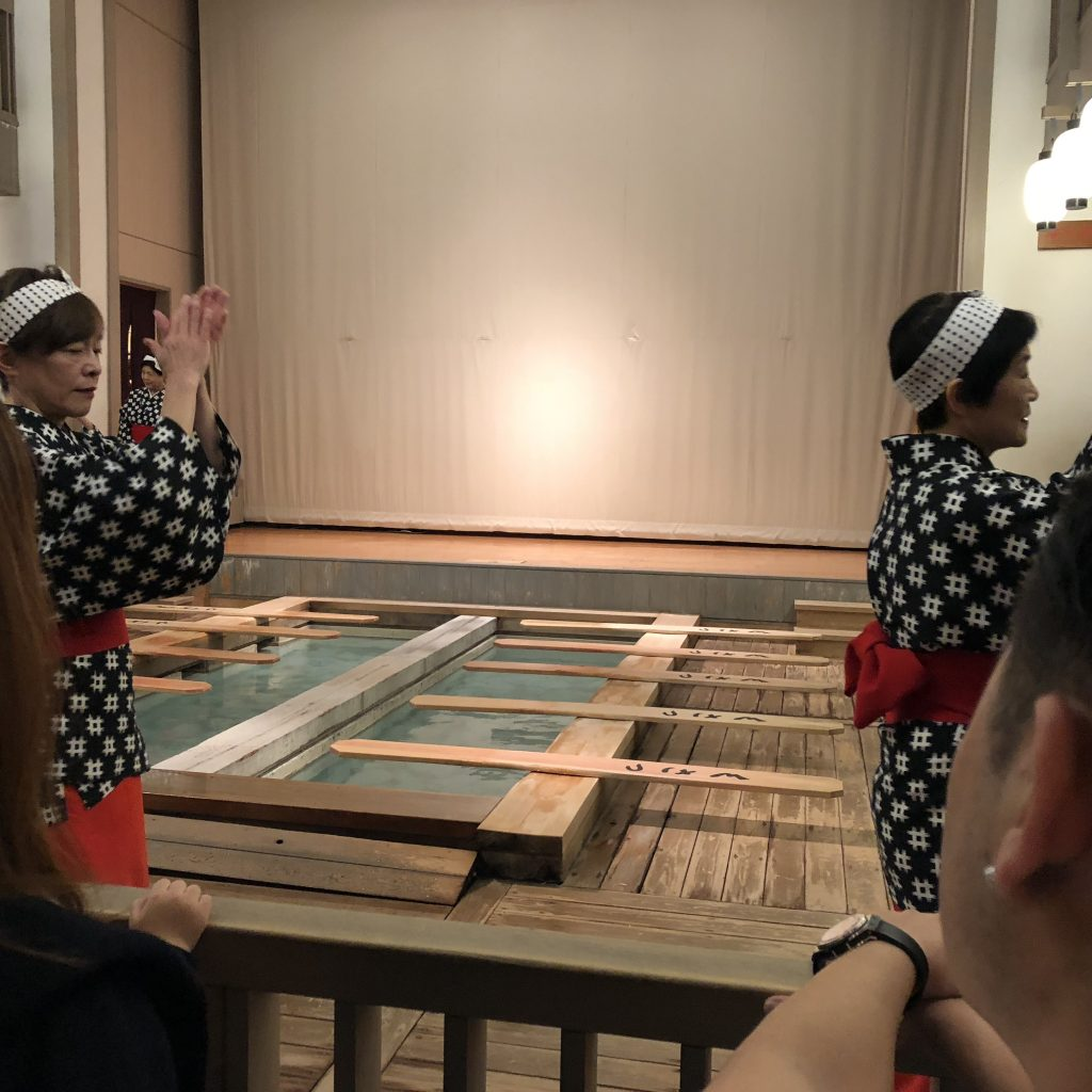 A photo of the women walking around the pool in a circle clapping their hands.