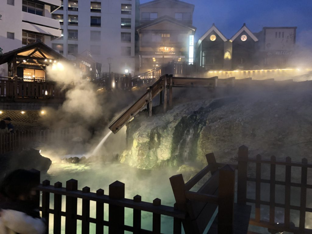 A night view of the lower end of the hot water fields. You can see a wooden chute bringing water down, and the whole thing is wreathed in hot steam.