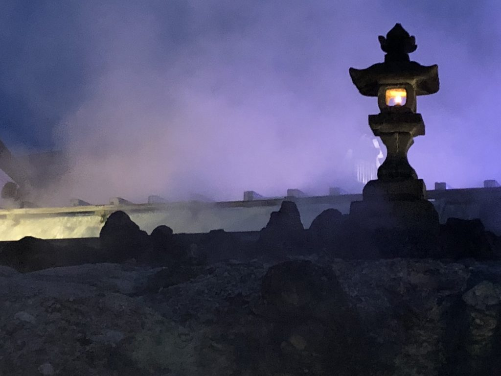 A lit stone lantern at night. Purple steam rises up behind it.