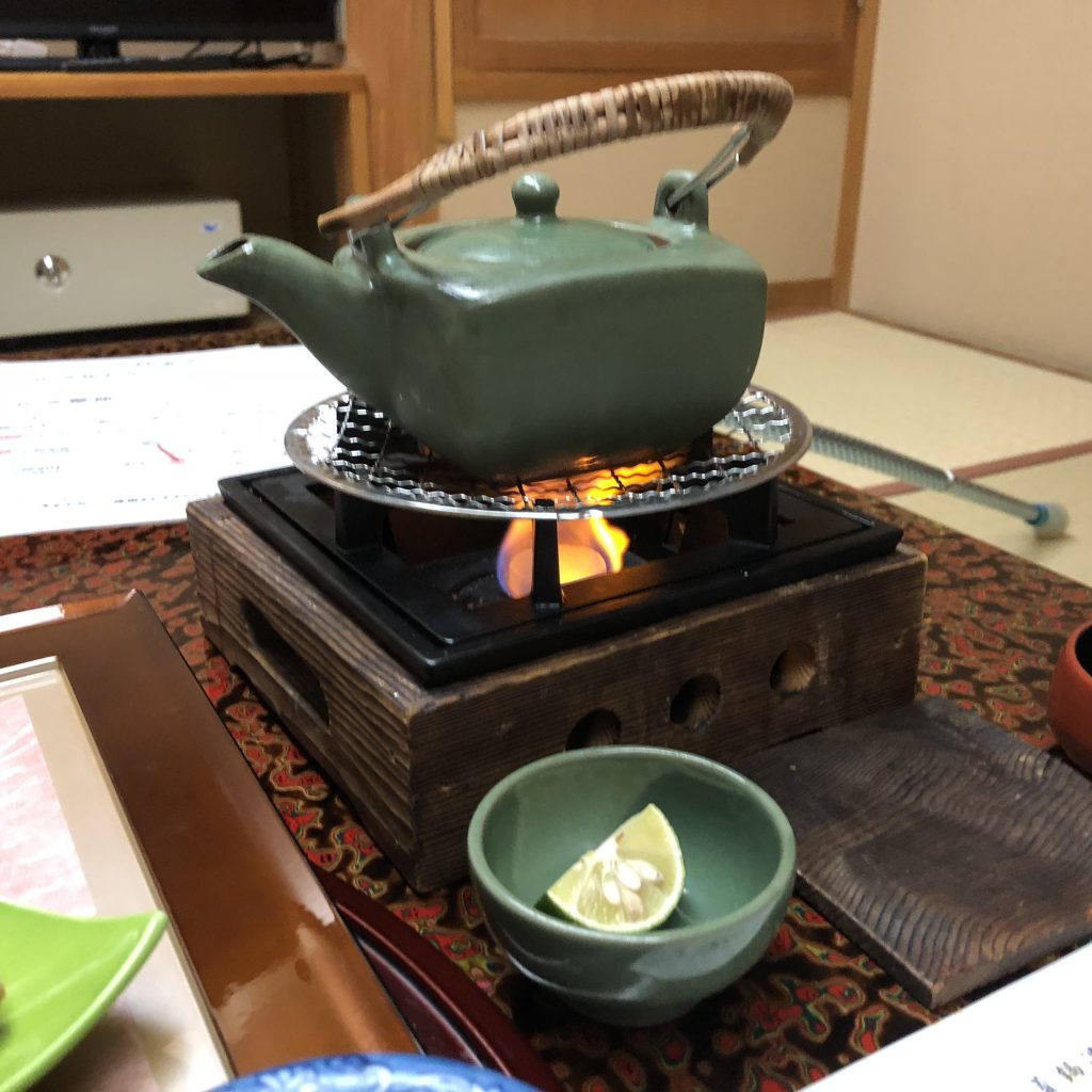 A green teapot on a brazier.