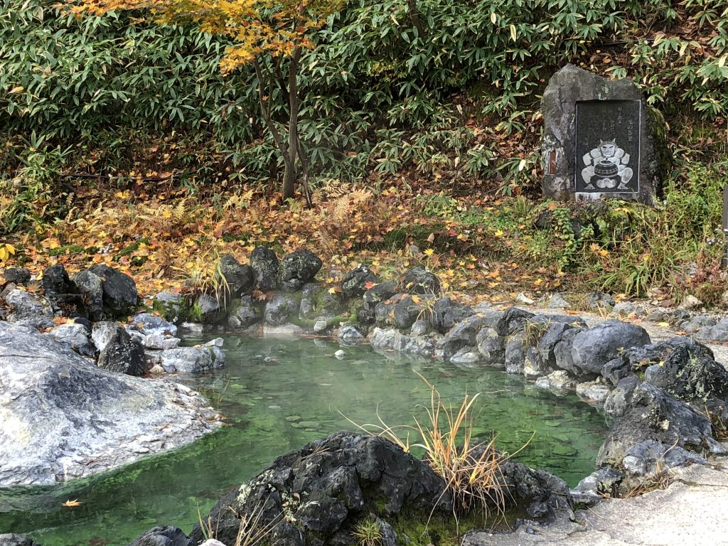 A small pool ringed with stone. You can see steam rising from the pool. In the background, there is a carving of an oni/devil with a poem carved above it.