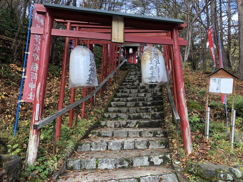 Steps leading up to a small Shinto shrine on a wooded hill. Red wooden torii gates line the stairs, and lanterns hang from them.