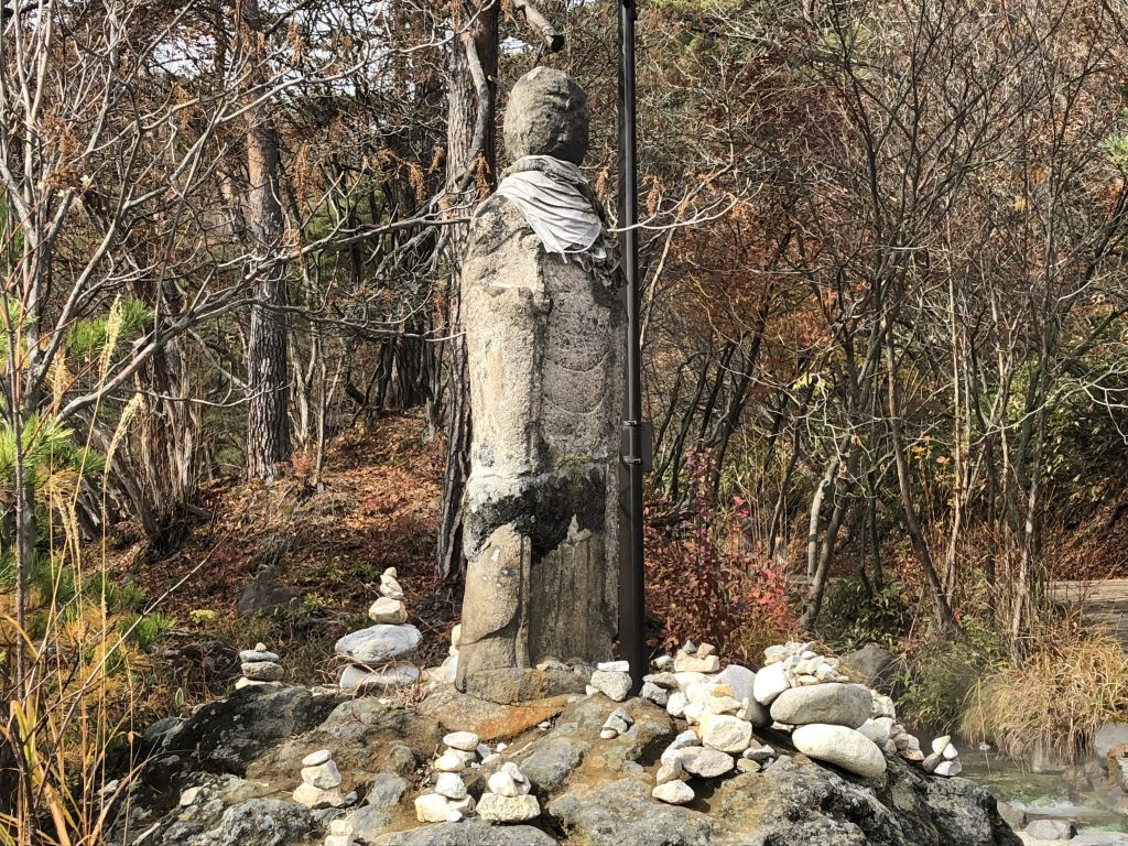 A very, very old statue. Most of its features have been worn away, but the tattered remains of a bib can still be seen around its neck, identifying it as Jizo. Small stacks of rocks have been left around it by adherents.