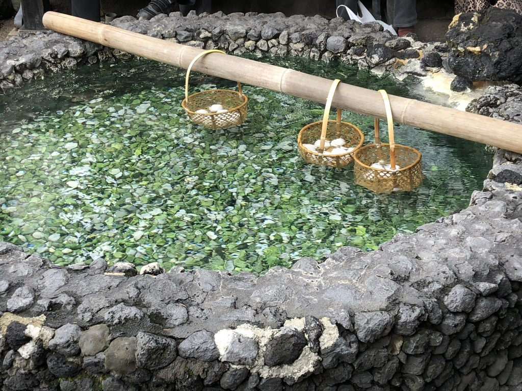 A long bamboo rod is suspended over a rock pool full of hot spring water. Three baskets full of eggs are hanging from the rod.