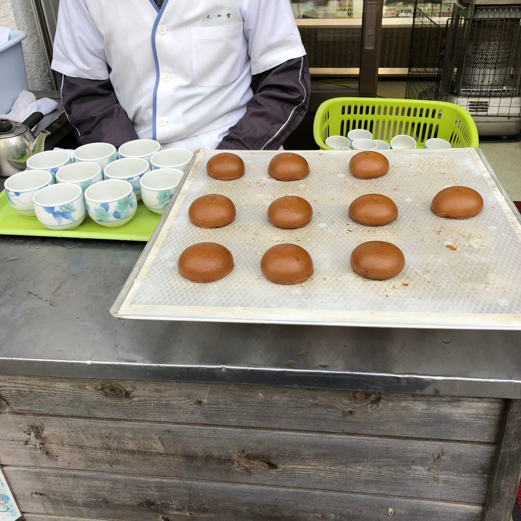 A close-up of the counter at a manjuu stand. There is a tray full of small brown manjuu and a tray full of empty teacups.
