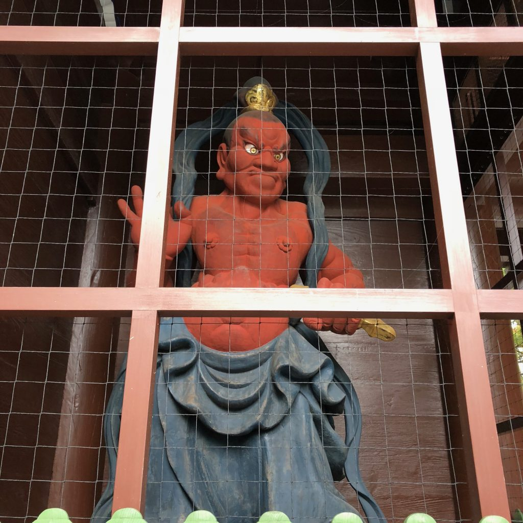 A red statue behind protective lattice. He's muscled and scary and his mouth is closed.