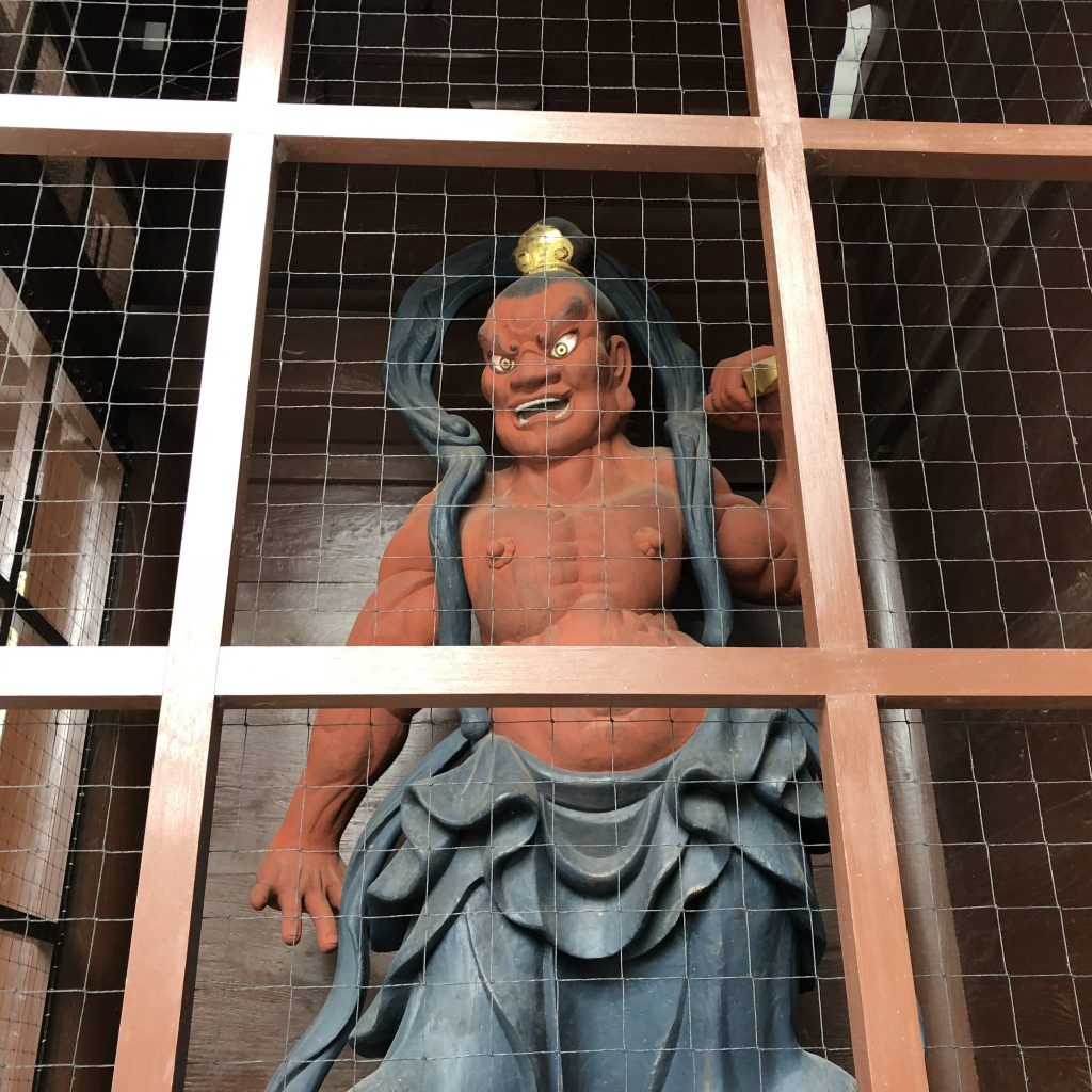 A red statue behind protective lattice. He's muscled and scary and his mouth is open.