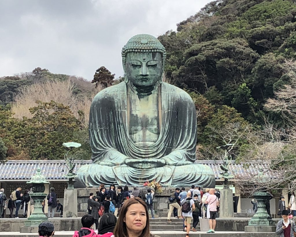 A photo of the daibutsu from the front. There are people all over.