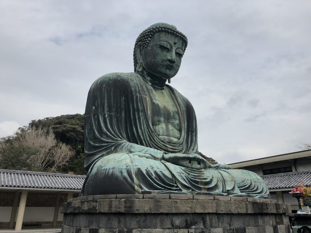A photo of the great Buddha of Kamakura. It is a seated bronze statue that has a lovely patina. He is sitting in the lotus position.