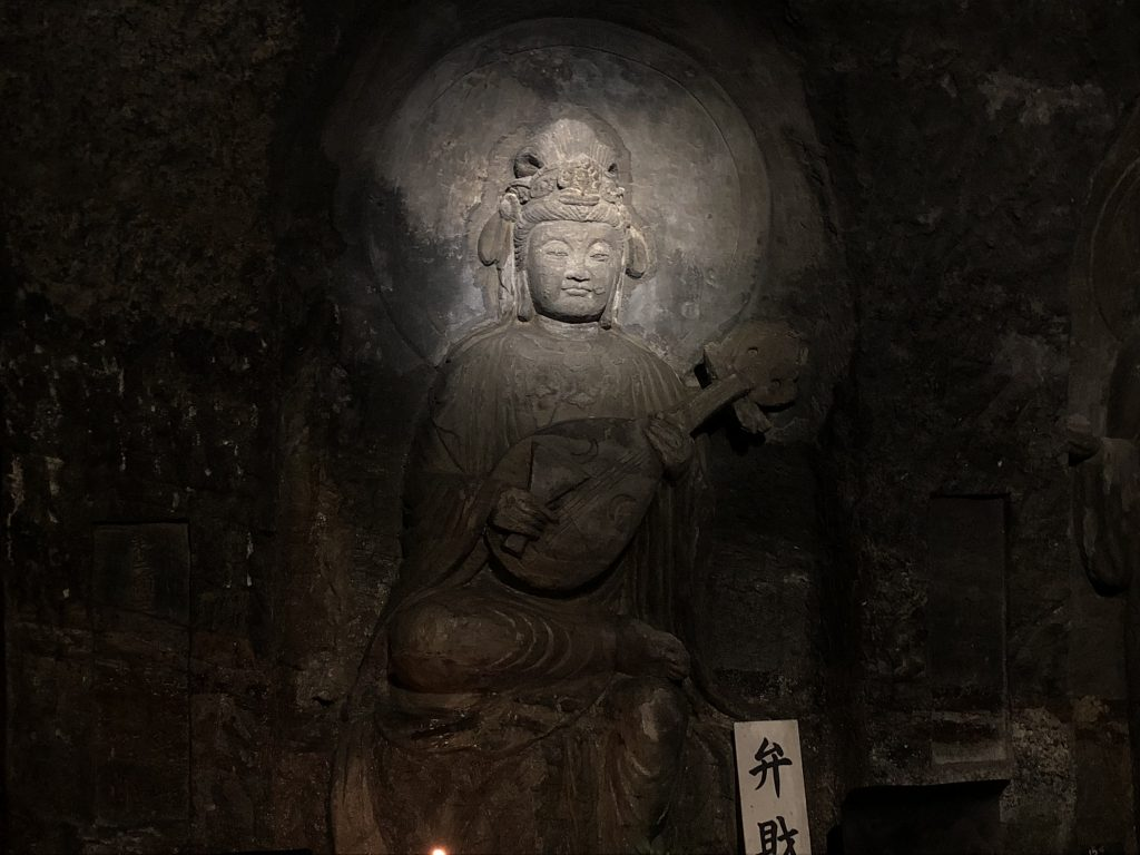 A statue of a woman holding a lute carved into a cave wall.