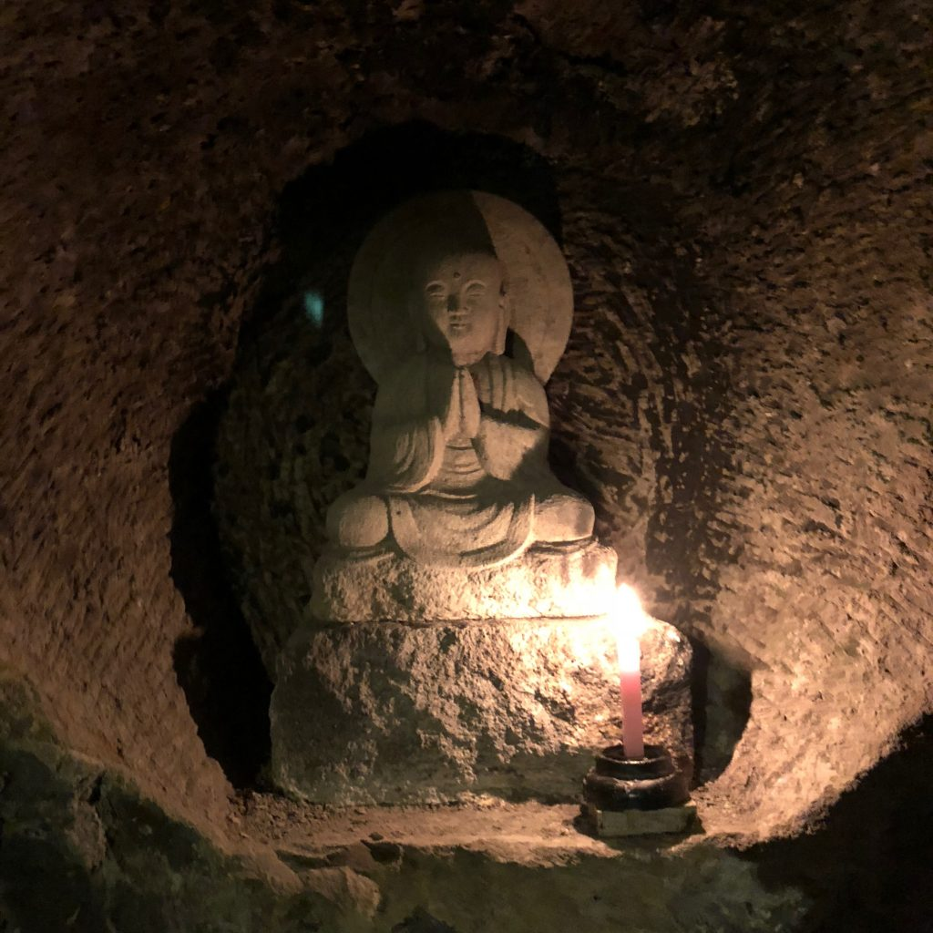 a small statue of jizo set into the wall.