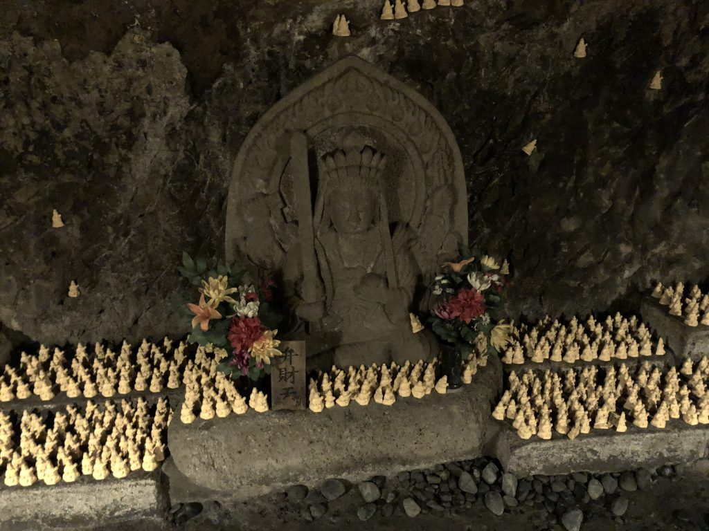 A small statue of Benzaiten. There are hundreds of tinier votive statues scattered around her.