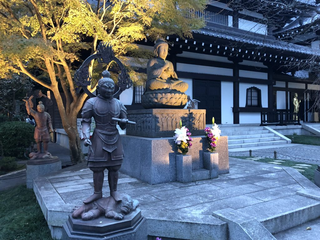 A statue of the historical Buddha surrounded by statues of guardian deities.