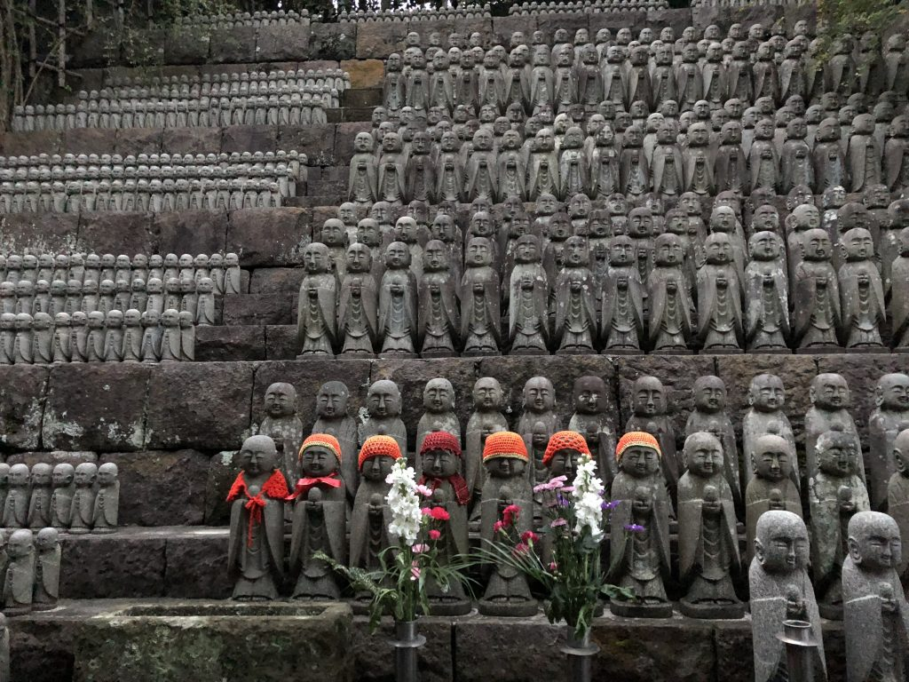 Several outdoor stone shelves of middling to small Jizo statues. At least a hundred are in the picture.