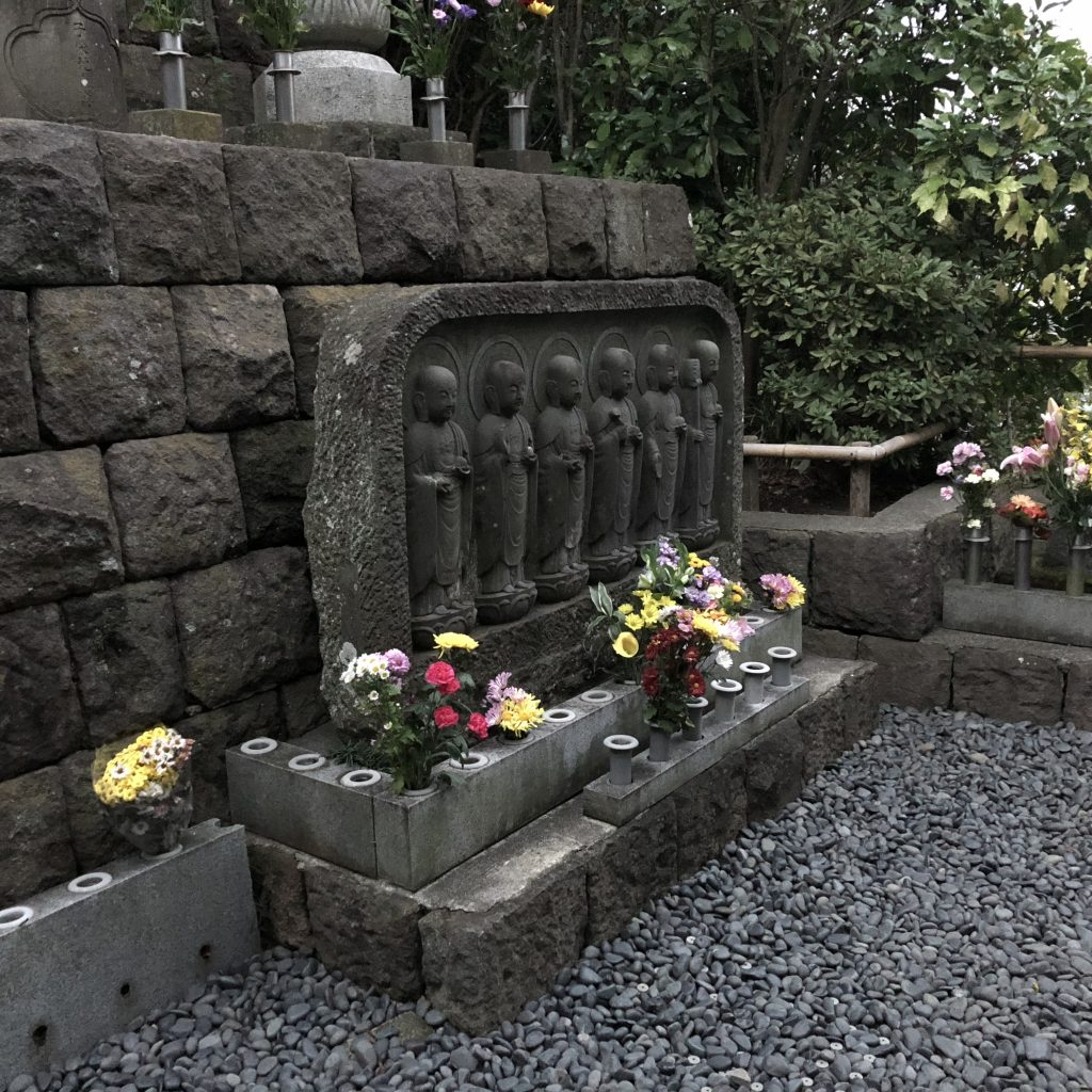 A statue of several Jizo in a row, each in a different position.
