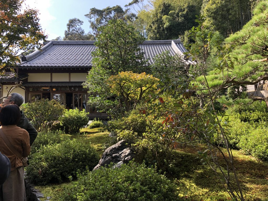 A traditional temple hall surrounded by trees.