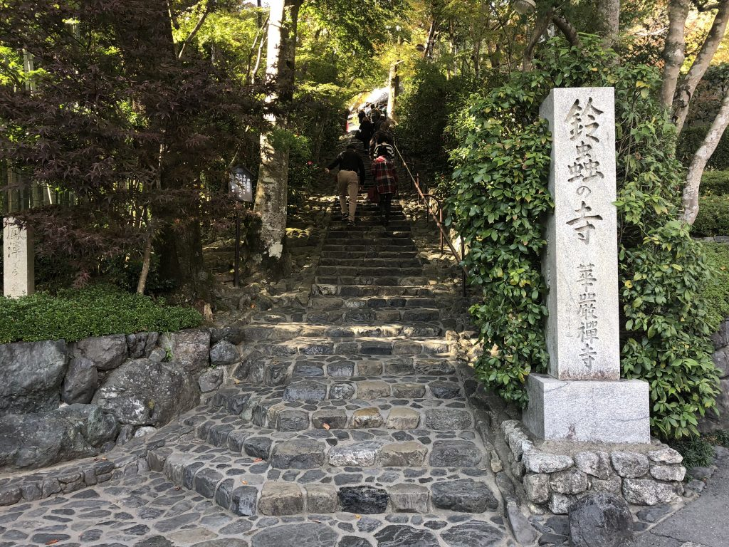 A flight of stone steps going up into the forest. A stone column in the front has the name of the temple on it.