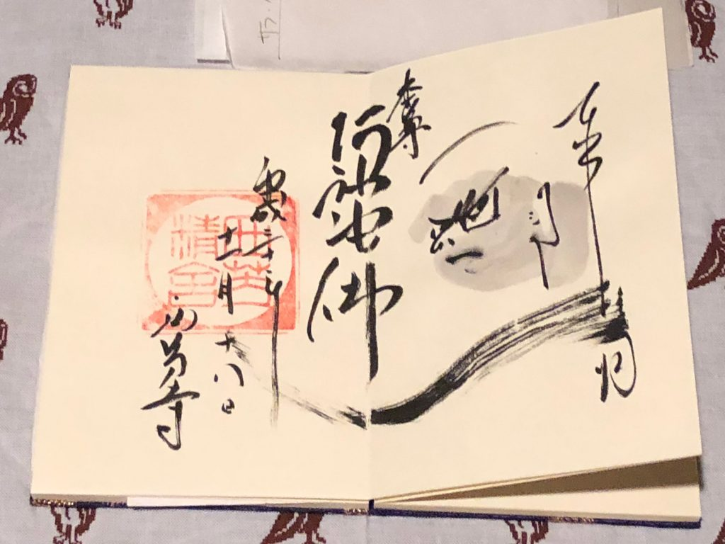 A goshuin spanning two full pages. The calligraphy is very artfully done, and contains an illustration of a severe-looking man.