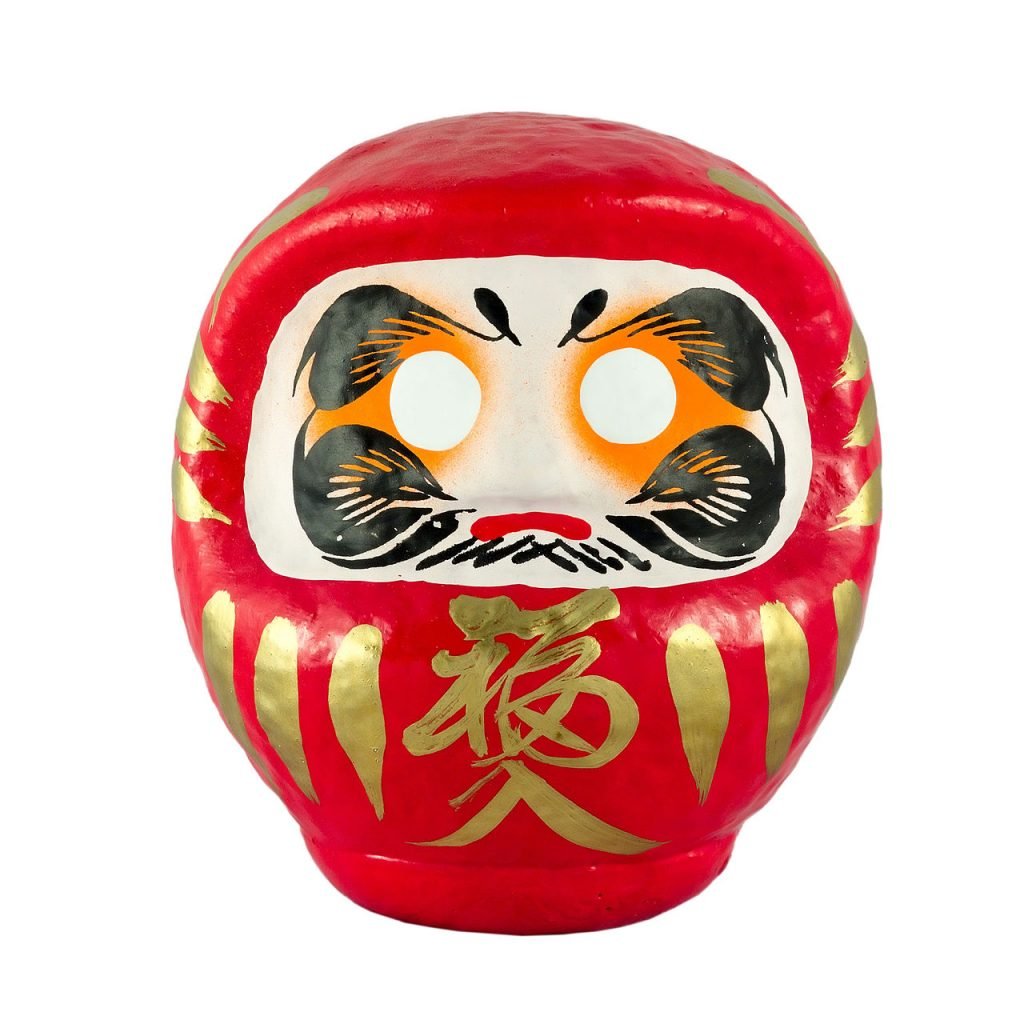 A daruma doll. It is round with a red body and hood, golden accents, and wide white eyes.