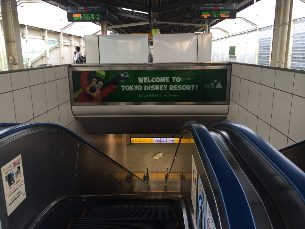 A sign welcoming guests to Tokyo Disneyland in the train station.