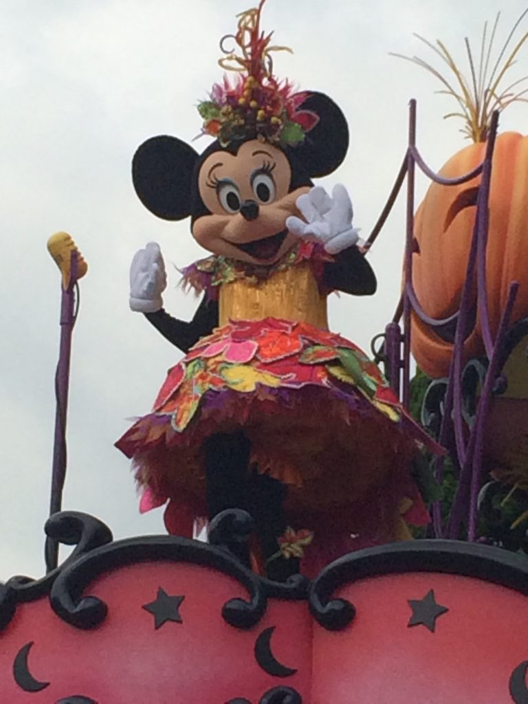 Minnie in a very cute harvest-themed dress, waving to the crowd.