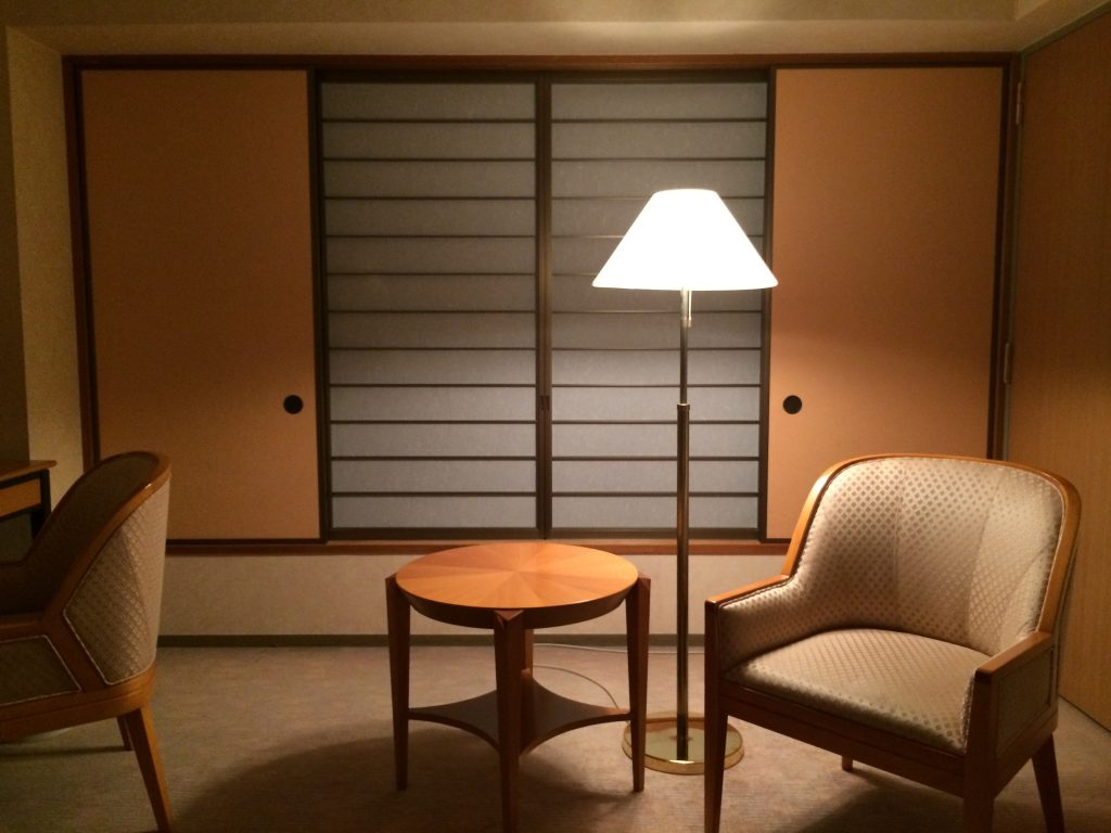 A picture of a hotel room. It has traditional Japanese sliding windows.