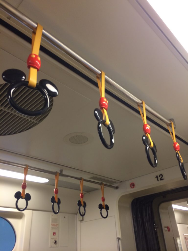The hanging handles on this train are shaped like Mickey's head.