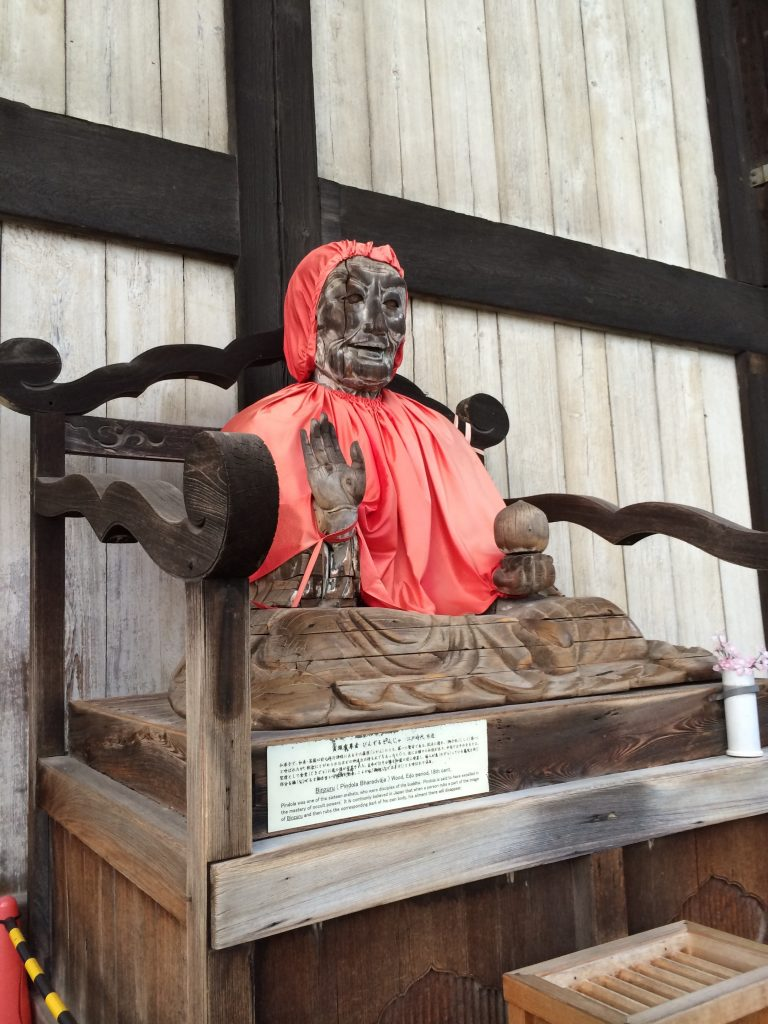 A dilapidated wooden statue wearing a red cloak.