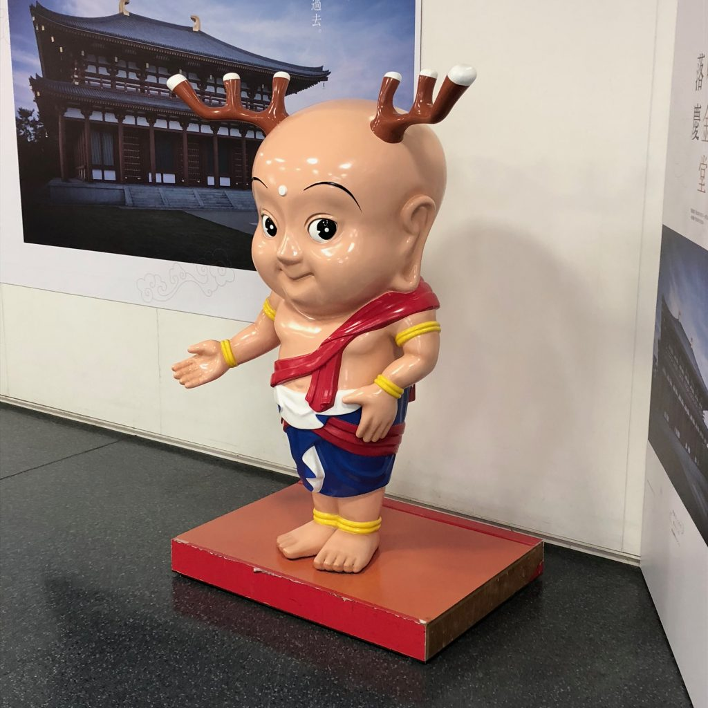 A terrifying baby-looking buddha with antlers.
