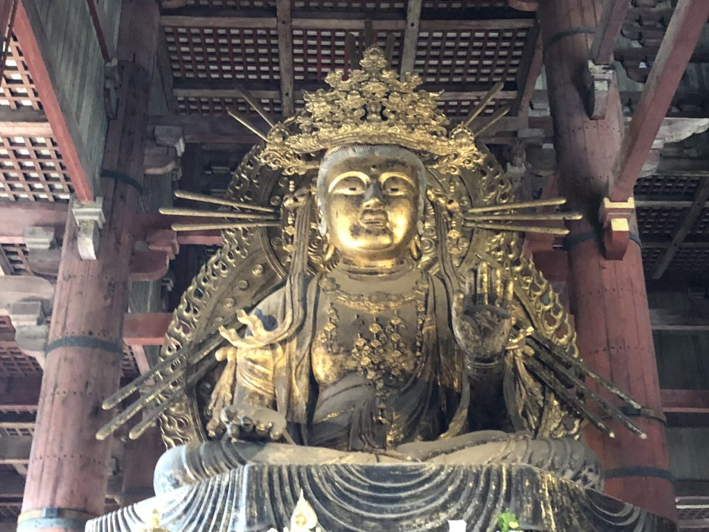 A golden statue of a seated Kannon.