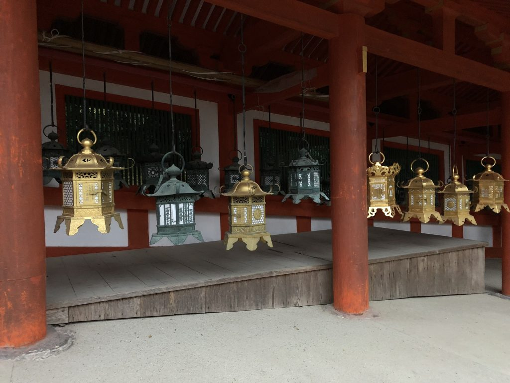 Metal lanterns hanging from the roof of the shrine. They are green and brass.
