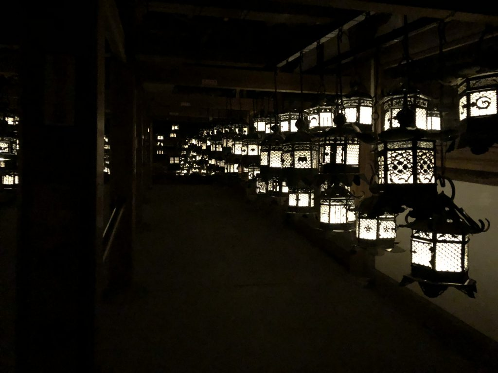 A room full of lit hanging lanterns and mirrors.