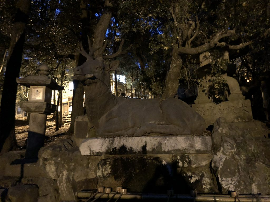 A massive stone deer reclining next to a stone lantern.