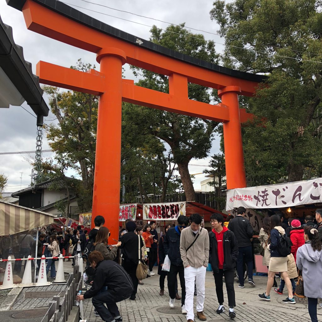 A large torii gate surrounded by food and souvenir stalls.