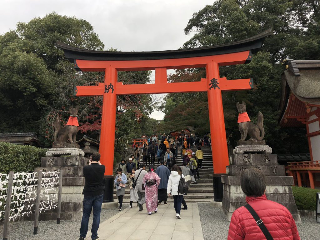 A large red torii surrounded on both sides by stone foxes.