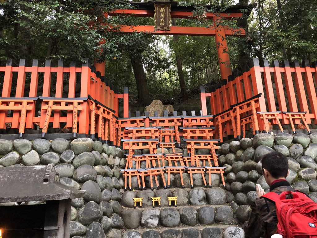 A large torii with a stone altar containing a few dozen tiny torii.