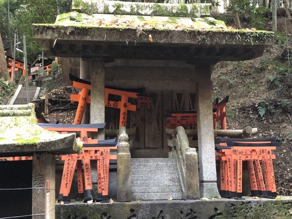 A mossy stone altar full of stacks of tiny torii with wishes written on them.